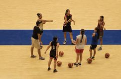 Women training basketball in coliseum stock photography