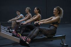 Women training rowing in gym with exercises machines and pull ro. Pe Royalty Free Stock Photos