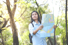 Women traveler with backpack checks map to find directions in th Stock Photos