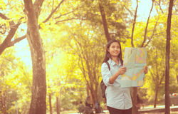 Women traveler with backpack checks map to find directions in th Royalty Free Stock Photo