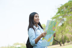 Women traveler with backpack checks map to find directions in th Royalty Free Stock Photography