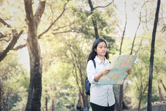 Women traveler with backpack checks map to find directions in th Royalty Free Stock Image