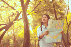 Women traveler with backpack checks map to find directions in th Royalty Free Stock Images