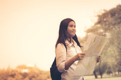 Women traveler with backpack checks map to find directions in th Stock Photo