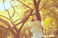 Women traveler with backpack checks map to find directions in th Stock Photography