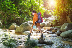 Women traveler with backpack checks map to find directions in water fall Stock Photo