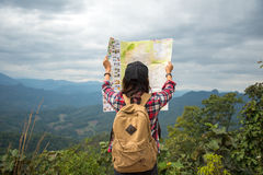 Women traveler  with backpack checks map. To find directions in wilderness area Royalty Free Stock Photo