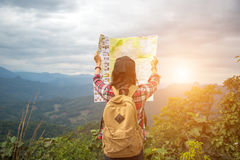 Women traveler with backpack checks map. To find directions in wilderness area Stock Image