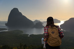 Women traveler with backpack checks map to find directions. In wilderness area Royalty Free Stock Photo