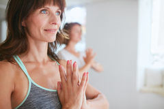 Women in tree pose yoga with Namaste. Close up shot of happy mature women doing yoga looking away smiling. Women in yoga pose vrikshasana using Namaste royalty free stock image
