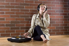Women in trenchcoat listens music. Young women in a trenchcoat listens to music of a record player Royalty Free Stock Photos