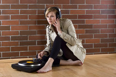 Women in trenchcoat listens music Stock Photo