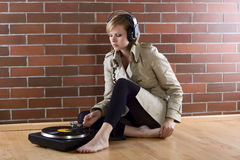 Women in trenchcoat listens music. Young women in a trenchcoat listens to music of a record player Stock Images