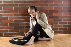 Women in trenchcoat listens music. Young women in a trenchcoat listens to music of a record player Royalty Free Stock Photo