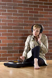 Women in trenchcoat listens music. Young women in a trenchcoat listens to music of a record player Stock Photography