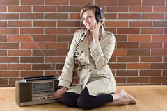 Women in trenchcoat listens to a vintage radio. Young women in a trenchcoat listens to music of a vintage radio Royalty Free Stock Images