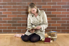 Women in a trenchcoat reads book. Women in a trenchcoat sitting next to a pile of books and reads one Stock Photography
