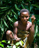 Women from a tribe of pygmies sit in the forest. Stock Images