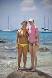 Women in the tropics. Two women in bikinis standing on a rock in the tropics with sailboats in the background Stock Photography