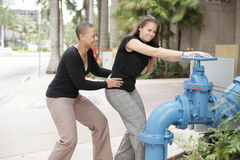 Women trying to turn off the water Stock Photos