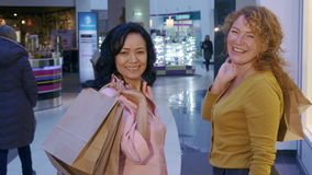Women turn back at the mall. Two women turning back to the camera at the mall. Caucasian and asian ladies finishing their shopping. Two attractive female stock video