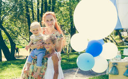 Women and two child  - boy and girl near balloons. Summer day on picnic in city park. Royalty Free Stock Photos
