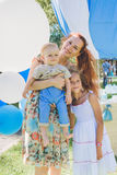 Women and two child  - boy and girl near balloons. Summer day on picnic in city park. Royalty Free Stock Image