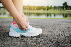 Women tying sport shoe prepare jogging at park. Stock Photo
