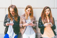Women typing on mobile phones. Girls typing on mobile phones - Three friends holding mobile phones and chatting - Youth,technology and comunication concepts Stock Photography