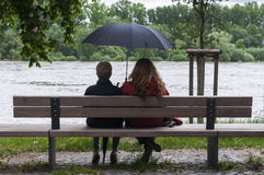 Women with umbrella on a bench Royalty Free Stock Image