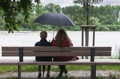 Women with umbrella on a bench Stock Photos