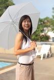 Women and umbrella beside swimming pool Stock Photo