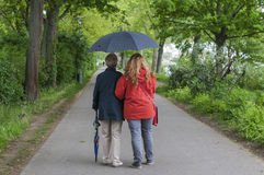 Women with umbrella walk for a way along Stock Image