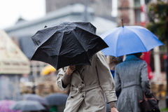 Women with umbrellas walking in the rain. Women with rain coats umbrellas walking in the rainy city Royalty Free Stock Photo