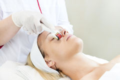 The woman undergoes the procedure of medical micro needle therapy. The women undergoes the procedure of medical micro needle therapy with a modern medical Royalty Free Stock Photos
