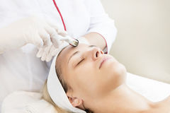 The woman undergoes the procedure of medical micro needle therapy. The women undergoes the procedure of medical micro needle therapy with a modern medical Stock Images