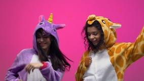 Women in unicorn and giraffe pajamas dancing on carnival party, having fun. Stock footage stock video