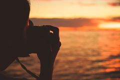 A women use camera to take shot sea and sunset between travel. Women use camera to take shot sea and sunset between travel royalty free stock photo