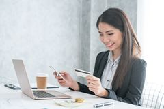 Women use laptops and mobile phones to shop online and pay by cr stock photography