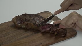 Women use a silver fork and knife to cut a beefsteak to prepare for dinner