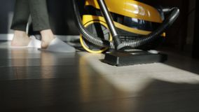 Young attractive housewife vacuuming in the room. Women use vacuum cleaner to cleaning the floor in living room at home during end of year clean. Housework stock footage