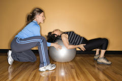 Women Using Balance Ball. Woman steadies a balance ball for another woman lying back on it at the gym. Horizontal shot Royalty Free Stock Photos