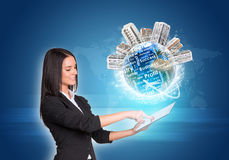 Women using digital tablet. Earth with buildings Stock Photography