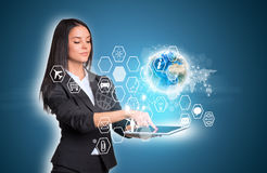 Women using digital tablet and Earth with hexagons Stock Photo