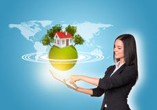 Women using digital tablet and Earth with house Royalty Free Stock Images