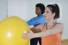 Women Using Exercise Balls In Fitness Class Stock Photography