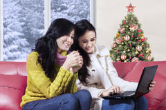 Women using laptop on sofa with christmas tree background Stock Photos