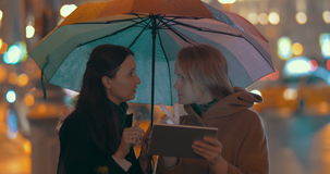 Women using pad to find way in the city. Two young women with umbrella using online map on tablet computer to find the way in the evening city stock video footage