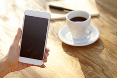 Women using smartphone. Close-up, coffee and planning book on the background Royalty Free Stock Photo