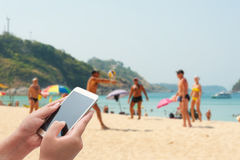 Women using smartphone top on blurred blue sea with some people. Relax on the white sand beach - Can be used for display or montage your products Stock Photo